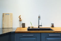 Modern sink with wooden cutting board in kitchen room Stock Photos