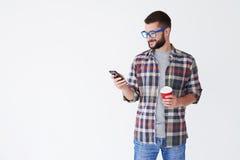 Modern skäggig man i blåa exponeringsglas som dricker kaffe och smsar nolla Royaltyfria Bilder