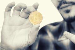 Modern skäggig man som rymmer en bitcoin, nya cryptocurrencypengar i hans hand och pekar ett finger på det royaltyfri fotografi