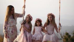 Modern skakar hennes döttrar på en gunga under ett träd stock video