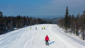 Modern ski resort in pine forest aeria, view from above. Footage. Young group of people snowboarding and skiing down the. Modern ski resort in pine forest aeria royalty free stock photos