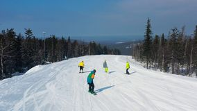 Modern ski resort in pine forest aeria, view from above. Footage. Young group of people snowboarding and skiing down the. Modern ski resort in pine forest aeria royalty free stock images