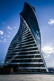 Modern skyscraper in the form of spiral on a background of blue sky royalty free stock photos