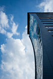 Modern skyscraper reaching the blue sky with clouds Stock Photos