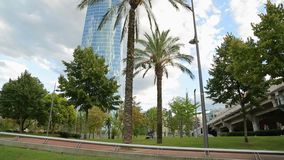 Modern skyscraper in resort city, park with exotic trees outside office building. Stock footage stock video footage