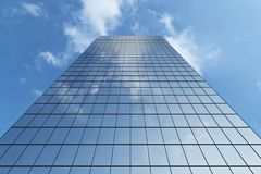 Modern skyscraper under blue sky with clouds. Bottom view of modern business skyscraper in business district in day sunlight under blue sky with clouds raising Stock Photos