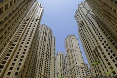Modern skyscrapers, high-rise buildings, architecture raising to the sky, upwards view, blue sky, clear sky, urban landscape. Yellow and blue, Dubai, modern royalty free stock photos