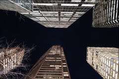 Modern skyscrapers at night. Low angle view looking up to top of modern skyscrapers illuminated at night Stock Photos