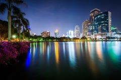Modern skyscrapers and palm trees along Lake Rajada at night, at Royalty Free Stock Photo