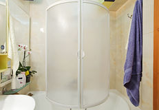 Modern small shower-bath with blue towel. And shower-bath royalty free stock image