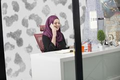 Modern smart female Islamic office worker talking on phone.  Stock Images