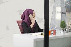 Modern smart female Islamic office worker talking on phone.  Stock Photos