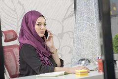 Modern smart female Islamic office worker talking on phone.  Royalty Free Stock Photos