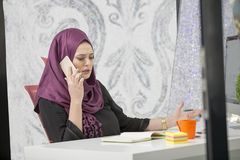 Modern smart female Islamic office worker talking on phone.  Royalty Free Stock Image