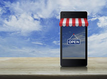 Modern smart mobile phone with on line shopping store graphic. And open sign on wooden table over blue sky Stock Image