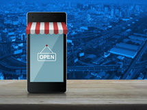 Modern smart mobile phone with on line shopping store graphic an. D open sign on wooden table over city tower and expressway Royalty Free Stock Photography