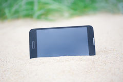Modern smart phone with blank screen in sand Royalty Free Stock Photo
