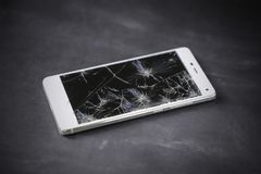 Modern smart phone with broken screen. Modern smart phone with broken screen on the dark table stock photo