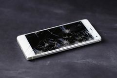 Modern smart phone with broken screen. Modern smart phone with broken screen on the dark table stock photography