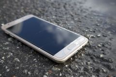 Modern smart phone with cracked screen glass lying in a puddle stock photo