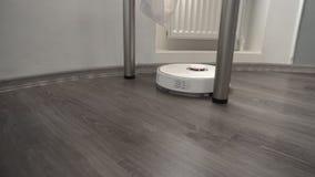 Modern smart robotic dammsugare gör ren laminatgolvet i lägenhet arkivfilmer