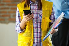 Modern and smart woking women. Female engineer looking at the mobile phone close up Stock Image