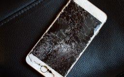 Modern smartphone with broken screen. Modern smartphone with highly broken screen on the black leather chair royalty free stock photo