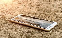 Modern smartphone with broken screen. Modern smartphone with highly broken screen dropped on the asphalt stock photography
