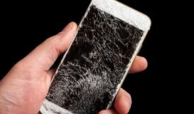 Smartphone with broken screen in men hand. Modern smartphone with highly broken screen in men hand on black background royalty free stock image