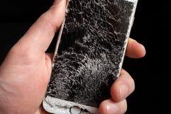 Smartphone with broken screen in men hand. Modern smartphone with highly broken screen in men hand on black background stock image