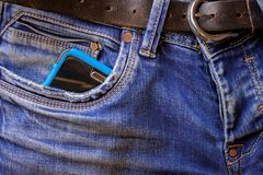 Smartphone sticks out of a pocket of blue jeans stock images
