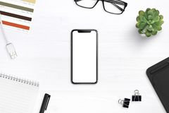 Modern smartphone mockup on a desk surrounded by supplies stock photography