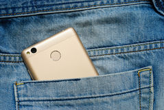 Modern smartphone in the old jeans pocket. Stock Images