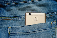 Modern smartphone in the old jeans pocket. Stock Image