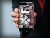 Modern smartphone with touchscreen interface. Wireless communications concept: businessman holding a modern smartphone with touchscreen interface Royalty Free Stock Photography