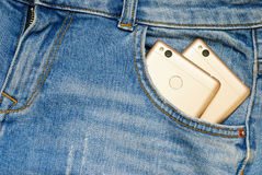 Modern smartphones in the old jeans pocket. Stock Images
