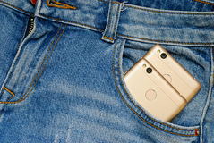 Modern smartphones in the old jeans pocket. Royalty Free Stock Photos