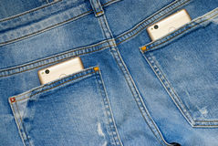 Modern smartphones in the old jeans pockets. Stock Image