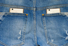 Modern smartphones in the old jeans pockets. Stock Photos