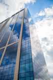 Modern smoked glass office building against a blue cloudy sky. Stock Photos