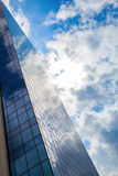 Modern smoked glass office building against a blue cloudy sky. Royalty Free Stock Photos