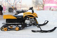 Modern snowmobile stands near the ice town on the street of the Royalty Free Stock Images
