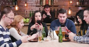 Modern society problem: friends in a pub all look at their smartphones