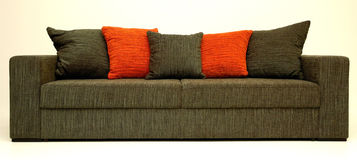 Modern sofa. Modernly designed using straight lines, covered with grey-orange textile on body and pillows, for sitting and sleeping Royalty Free Stock Photos