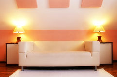 Modern sofa. A modern-style white sofa with lamps on each side; warm colors used in the decor Stock Images