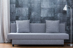 Modern sofa and concrete wallpaper Stock Images