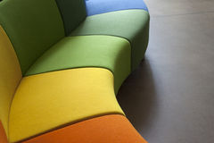 Modern sofa. Detail of a curved sofa in green, orange and yellow Stock Image