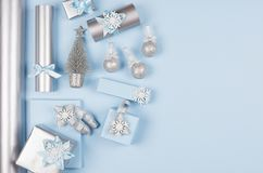 Modern soft minimalist christmas background with copy space - pastel blue and silver metallic gift boxes with shiny ribbons. Modern soft minimalist christmas royalty free stock images