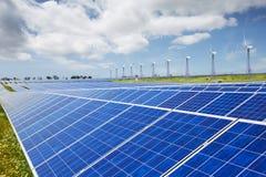 Modern sol- station med blåa paneler och windfarm med vindtur Arkivfoton