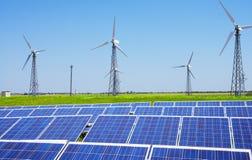 Modern sol- station med blåa paneler och windfarm med vindtur Fotografering för Bildbyråer
